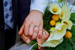 Mãos com o kala feliz dos recém-casados dos anéis de ouro do casamento e das flores do ramalhete Imagens de Stock