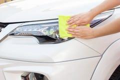 Mãos com o pano amarelo do microfiber que limpa o carro branco grande Fotografia de Stock