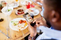 Mãos com o smartphone que representa o alimento no restaurante Imagem de Stock Royalty Free
