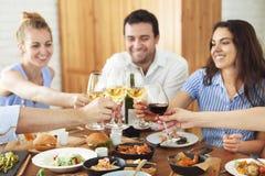 Mãos com o vinho branco que brinda sobre a tabela servida com alimento Imagens de Stock Royalty Free