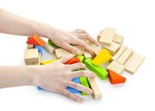 Mãos com os brinquedos de madeira do bloco Foto de Stock