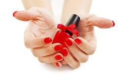 Mãos com os pregos e verniz para as unhas vermelhos bonitos Imagens de Stock
