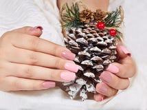 Mãos com os pregos manicured cor-de-rosa artificiais longos que guardam uma decoração do Natal do pinho fotos de stock
