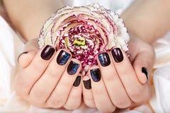 Mãos com os pregos manicured curtos coloridos com verniz para as unhas e a flor roxos escuros Fotografia de Stock Royalty Free