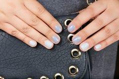 Mãos com os pregos manicured curtos coloridos com verniz para as unhas cinzento imagem de stock royalty free
