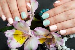 Mãos com os pregos manicured curtos coloridos com verniz para as unhas cor-de-rosa e verde fotografia de stock