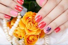 Mãos com os pregos manicured curtos coloridos com verniz para as unhas cor-de-rosa e vermelho foto de stock