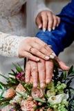 Mãos com os recém-casados felizes dos anéis de ouro do casamento no o fundo do ramalhete Imagem de Stock