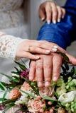 Mãos com os recém-casados felizes dos anéis de ouro do casamento no o fundo do ramalhete Fotos de Stock Royalty Free