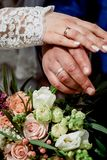 Mãos com os recém-casados felizes dos anéis de ouro do casamento no o fundo do ramalhete Imagens de Stock Royalty Free