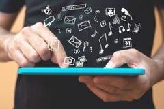 Mãos com tablet pc e vários ícones da garatuja Fotografia de Stock Royalty Free