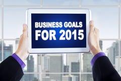 Mãos com a tabuleta que mostra objetivos de negócios para 2015 Imagens de Stock