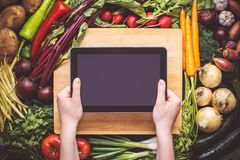 Mãos com a tabuleta sobre o fundo orgânico fresco dos vegetais imagens de stock royalty free