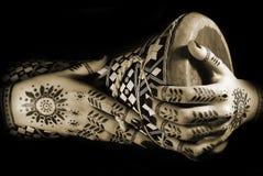 Mãos com tatuagem oriental e cilindro fotografia de stock