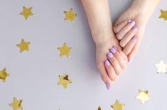 Mãos com tratamento de mãos roxo em um fundo cinzento com asteriscos imagens de stock