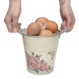 Mãos com uma cubeta e os ovos Imagem de Stock Royalty Free