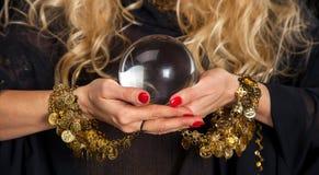 Mãos da bola de cristal e do caixa de fortuna foto de stock