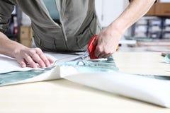 Mãos da costureira que cortam a tela com tesouras imagem de stock