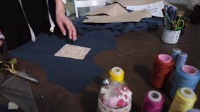 Mãos da costureira que unem a decoração para cortar o teste padrão video estoque