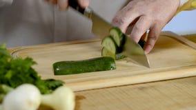 Mãos da cozinha grande da faca do cozinheiro um pepino verde fresco em uma placa de desbastamento de uma árvore vídeos de arquivo