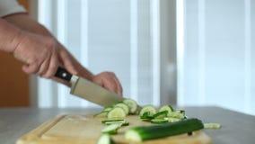 Mãos da cozinha grande da faca do cozinheiro um pepino fresco em uma placa de desbastamento de uma árvore vídeos de arquivo