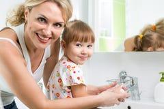 Mãos da criança da lavagem da mãe Fotos de Stock