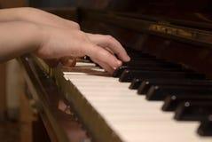 Mãos da criança no rolo do piano Fotos de Stock Royalty Free