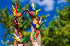 Mãos da criança pintadas em cores brilhantes no fundo da natureza do verão Imagem de Stock