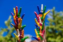 Mãos da criança pintadas em cores brilhantes no fundo da natureza do verão Fotos de Stock Royalty Free