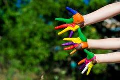 Mãos da criança pintadas em cores brilhantes no fundo da natureza do verão Fotografia de Stock