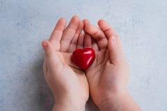 Mãos da criança que guardam o coração vermelho Carde para o dia de Valentim O dia do coração do mundo, dia de saúde de mundo, cui foto de stock