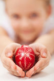 Mãos da criança que guardam o ovo da páscoa decorado tradicional Imagem de Stock