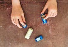 Mãos da criança que jogam com carros foto de stock