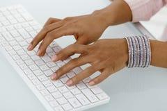 Mãos da dactilografia étnica da mulher de negócios Foto de Stock Royalty Free