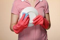 mãos da dona de casa com as luvas que guardaram o scrubberr Foto de Stock Royalty Free