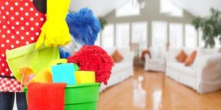 Mãos da empregada doméstica com ferramentas da limpeza