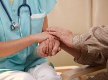 Mãos da enfermeira e do paciente idoso.