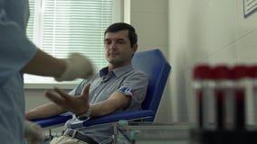 Mãos da enfermeira que prepara-se para tomar o sangue do paciente que senta-se na poltrona no fundo Teste borrado video estoque