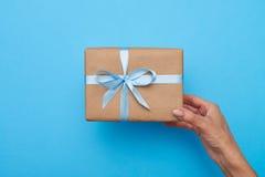Mãos da fêmea que guardam uma caixa de presente sobre o fundo azul imagem de stock royalty free