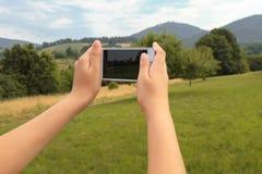 Mãos da jovem mulher com smartphone que tomam uma foto na natureza Fotografia de Stock Royalty Free
