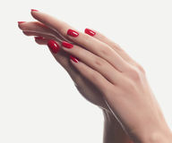 Mãos da jovem mulher com tratamento de mãos vermelho Fotos de Stock