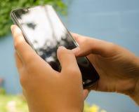 Mãos da jovem mulher com um smartphone foto de stock royalty free
