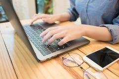 Mãos da jovem mulher que datilografam o laptop no café Mulher de funcionamento foto de stock royalty free