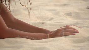 Mãos da jovem mulher que enterram na areia filme