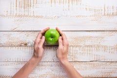 Mãos da jovem mulher que guardam Apple verde maduro no Tabletop de madeira do fundo da prancha branca outono liso da colheita da  Foto de Stock