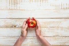 Mãos da jovem mulher que guardam Apple vermelho maduro no Tabletop de madeira do fundo da prancha branca outono liso da colheita  Imagens de Stock Royalty Free