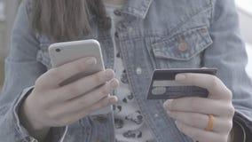Mãos da jovem mulher que guardam o cartão de crédito ao pagar vídeos de arquivo