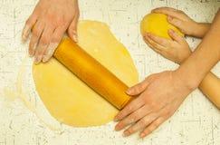 Mãos da mãe e do filho que amassam a massa na tabela foto de stock