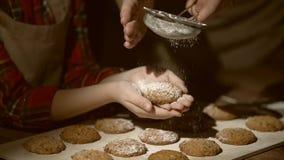 Mãos da mãe e da filha que preparam biscoitos filme