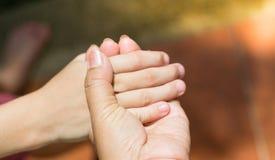 Mãos da mãe que guardam as mãos da criança tão firmemente está mostrando que quanto de seus amores concetp do amor imagens de stock
